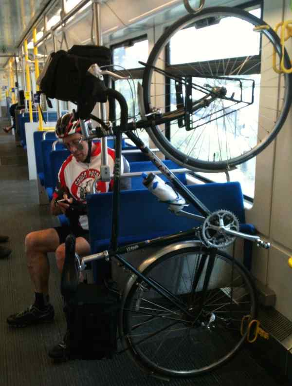 Now, notice where the bike is: hanging on the inside of a Caltrain car next to the bike rider.