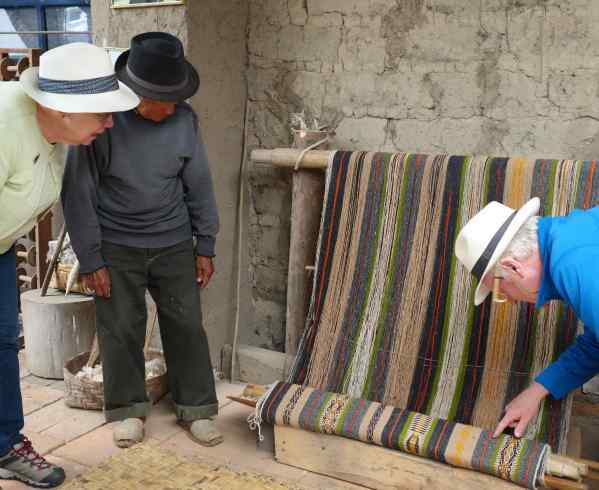 That's Señor Andrango showing Missy one of his weavings that is not yet finished.  That's Papa on the other side looking at the fine detail of the weaving.